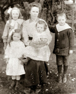 This image shows Lucy Atkinson c.1930s, wife of Arthur Atkinson with their children. The child on her knee is their son Leonard with Cecil standing on the right. The girl front left is Minnie with Madge standing rear left.