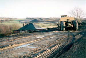 This image was taken on the 20 March 1994 and shows the line of the former railway and demolished bridge (in front of  the machine).  The old Glapwell pit tips can be seen as can on the horizon, the line of trees showing the line of the public footpath Palterton to Glapwell.