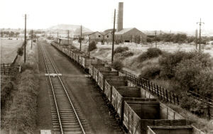 This image was taken on the 4 September 1955 and shows the Palterton and Sutton railway line from the bridge over Carr Lane, looking north towards Carr Vale and Bolsover Colliery.  The wagons are in the sidings by the side of the main line, that was used by coal wagons to and from Glapwell and Ramcroft Collieries.  This section was known as the Palterton and Sutton loop.  The bonus in this image is that the old Palterton Brickyard can be clearly seen.  In the distance can be seen an old Bolsover Colliery slag heap that was located to the west of New Bolsover.  This scene has long since disappeared.