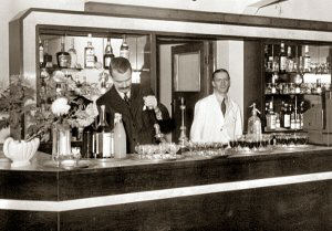 This image shows Anthony 'Tant' White behind the bar at the new Hare and Hounds pub on 'Opening Day'. The man from the Brewery is pulling the beer.