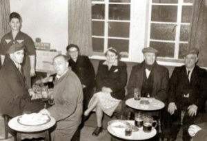 The new Hare and Hounds pub is open and the customers enjoy their first pint of beer, with sandwiches, of course! They are: Woman standing believed to be a Mrs Joe Brown from New Houghton. Seated L to R: Arthur Wragg. Graham (Chippy) Turner. Mary Holt nee Machin. Selina Wragg nee Turner (wife of Arthur and sister of Chippy), Edward (Ned) Holt (Mary's husband) and possibly Mr. Joe Brown (husband of woman standing).