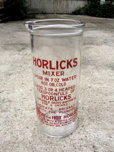 An image of a drinking glass that is believed to have been in use during World War 2 for a bedtime drink. To make the drink, you followed the instructions on the glass. Missing from this object is a plunger with holes in the bottom. One placed the plunger at the mouth of the jar and pushed it down into the glass, the Horlicks drink rising up through the holes in the plunger. You mixed the Horlicks Powder, with a little water and then pumped the plunger up and down when you added the hot water otherwise it would go into a hard lump.