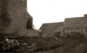 This image was taken halfway up the 'right of way' depicting the south side elevation and wall that surrounded the farmstead, stated to be 3 feet out of alignment prior to demolition. The farm building at the top of the driveway can clearly be seen with the two doors just in view. The outbuildings on the left irectly behind the old farmstead have since been demolished.