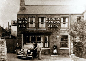 A modern image showing the Nags Head Inn. In the foreground is the licensee John William Spafford and his wife, posing with their car.