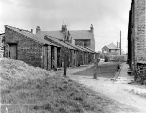 A 1960s image of part of Ten Row on the east side of Scotland Yard shortly prior to demolition. This is a view of the outside lavatories and coal houses that faced the respective houses. The nearest door, extreme left is the door to the lavatory for house number Ten and the next door is the door to the coal house. The rear of East View can be seen at the east end above the outside facilities and extreme centre the house where the Thacker family resided.