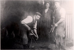 George Whitworth, blacksmith, seen with fellow blacksmith Mr. Askew and Mr. Skelton in the background