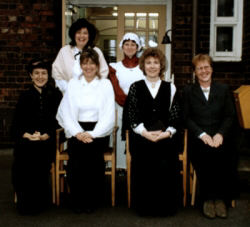 A group of teachers and staff 10 October 1996 - Victorian Day. Their identities L. to R. Front row are Andrea Fox - teacher, Lynn Tingle - teacher, Lesley Barringer - Head teacher and Sally Roberts - teacher.  Back row L. to R. Gill. Lewis - school secretary and Laura Robinson - Education care officer.